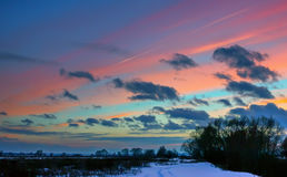 Paysage d'hiver avec les nuages roses au coucher du soleil Photos stock