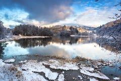 Paysage d'hiver avec un lac congelé, des arbres de Milou et des montagnes dans un jour nuageux image libre de droits