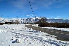 Paysage d'hiver couvert de neige près d'une route Photos libres de droits