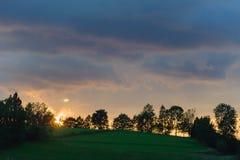 Paysage d'un grassfield et d'une colline au coucher du soleil Image libre de droits