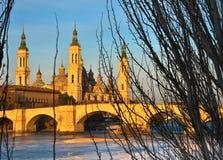 paysage d'un lever de soleil sur la basilique catholique pilaire à Saragosse sans compter que l'Ebro avec quelques arbres et usin image stock