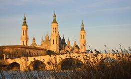 paysage d'un lever de soleil sur la basilique catholique pilaire à Saragosse sans compter que l'Ebro avec quelques arbres et usin photos stock