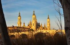 paysage d'un lever de soleil sur la basilique catholique pilaire à Saragosse sans compter que l'Ebro avec quelques arbres et usin photo libre de droits