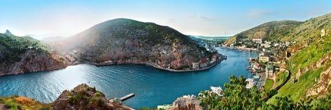 Paysage de baie de mer avec les montagnes de ciel bleu et l'herbe verte Photographie stock