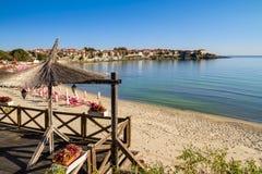 Paysage de bord de la mer - vue du café et de la plage sablonneuse avec des parapluies et des canapés du soleil dans la ville de  photographie stock