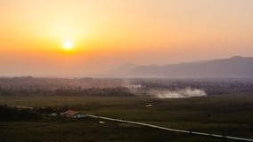 Paysage de coucher du soleil avec le ciel orange, la fumée et les silhouettes des collines à l'arrière-plan Image stock