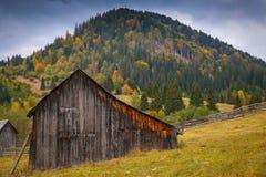 Paysage de paysage d'automne avec la forêt colorée, les barrières en bois et les granges de foin dans Bucovina, Roumanie image libre de droits