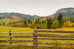 Paysage de paysage d'automne avec la forêt colorée, les barrières en bois et les granges de foin dans Bucovina, Roumanie images stock