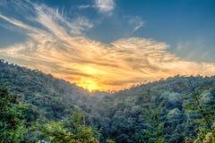 Paysage de forêt de montagne sous le ciel de soirée avec des nuages au soleil Image de HDR Photos stock