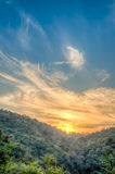 Paysage de forêt de montagne sous le ciel de soirée avec des nuages au soleil Image de HDR Photo stock