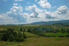 Paysage de jour d'été avec le champ, le ciel nuageux et le village Image stock
