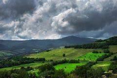 Paysage de jour d'été avec le champ, le ciel nuageux et le village Photo libre de droits