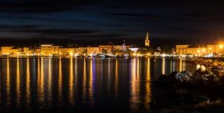 Paysage de l'illumination de nuit se reflétant dans la surface de l'eau dans l'obscurité Photos libres de droits