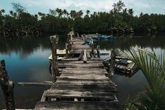 Paysage de la jetée en bois d'abandon traversant la rivière Le soleil lumineux Photographie stock