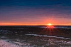 Paysage de la steppe en premier ressort avec la neige sur le fond du coucher du soleil Images libres de droits