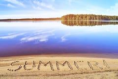 Paysage de lac morning avec l'été de mot écrit sur le sable de plage Photographie stock libre de droits