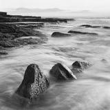 Paysage de lever de soleil d'océan avec des nuages et des roches de vagues Photographie stock