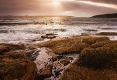 Paysage de lever de soleil d'océan avec des nuages et des roches de vagues Image libre de droits