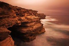 Paysage de lever de soleil d'océan avec des nuages et des roches de vagues Photo stock
