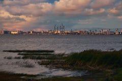 Paysage de mer avec la construction de routes et les grues de pont sur l'horizon dans la lumière de coucher du soleil images libres de droits