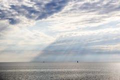 Paysage de mer avec une belle vue des nuages et des faisceaux du soleil qui font la voie par un nuage Photographie stock libre de droits