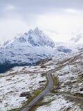 Paysage de Milou avec la route caillouteuse Crêtes pointues brumeuses de hautes montagnes à l'arrière-plan Photographie stock libre de droits