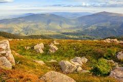 Paysage de montagne avec des pierres dans l'herbe sur le flanc de coteau et le bleu Photographie stock libre de droits