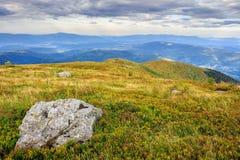Paysage de montagne avec des pierres dans l'herbe sur le flanc de coteau et le bleu Photo stock