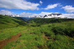 Paysage de montagne avec les prés et le soleil verts Image libre de droits