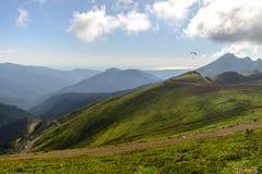 Paysage de montagne d'été avec le parapentisme dans la distance photos stock