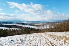 Paysage de montagne d'hiver avec le champ, le verger et le village dedans loin Photographie stock libre de droits