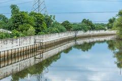 Paysage de mur de protection d'inondation avec des réflexions en bois de bateaux Images stock