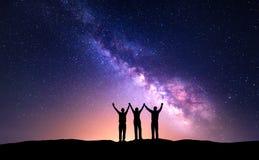 Paysage de nuit avec la manière laiteuse et la silhouette des personnes Photographie stock libre de droits