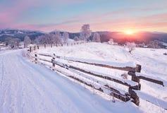 Paysage de pays d'hiver avec la barrière de bois de construction et la route neigeuse Photos libres de droits