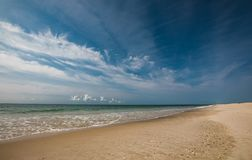 Paysage de plage vide sur Sunny Day avec le ciel bleu lumineux de vagues douces avec les nuages blancs Image libre de droits