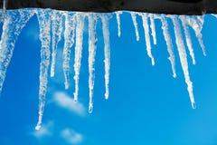 paysage de ressort avec des glaçons de glace pendant du toit de la maison Photos stock