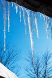 paysage de ressort avec des glaçons de glace pendant du toit de la maison Image libre de droits
