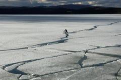 Paysage de ressort avec la dérive de glace sur le lac et un cycliste montant là-dessus photographie stock