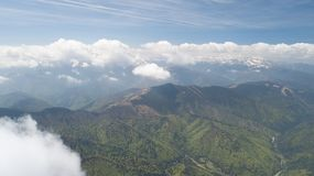 Paysage de ressort avec les crêtes de montagne couvertes de neige et de nuages Photographie stock libre de droits