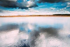Paysage de rivière ou de lac avec des réflexions de ciel nuageux dans l'eau images libres de droits