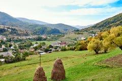 Paysage de village de pays de montagne avec les nuages et le ciel bleu Image stock