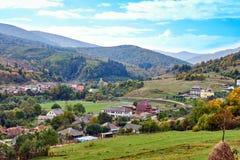 Paysage de village de pays de montagne avec les nuages et le ciel bleu Photographie stock