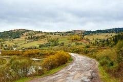 Paysage de village de pays de montagne avec les nuages et le ciel bleu Photographie stock libre de droits