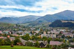 Paysage de village de pays de montagne avec les nuages et le ciel bleu Photos stock