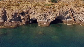 Paysage des grottes en falaises, montagnes, falaises Grottes profondes lavées à l'eau Îles grecques dans le méditerranéen banque de vidéos