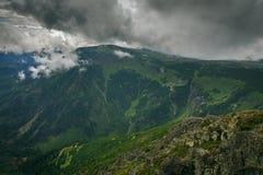 Paysage des montagnes couvertes de forêt verte pendant un nuage images stock