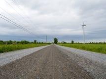 Paysage droit de route de gravier avec une turbine et des lignes électriques de vent image stock