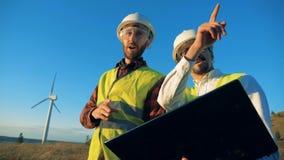 Paysage ensoleillé avec un moulin à vent avec deux spécialistes marchant par lui banque de vidéos