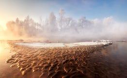 Paysage givré de matin d'hiver avec une petite rivière de forêt et un bas-fond arénacé brun, semblables à la lave Image libre de droits