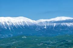 Paysage idyllique avec les prés verts frais et les dessus couronnés de neige de montagne Image stock